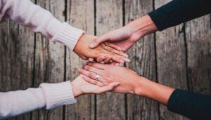 Women holding hands offer support for postpartum depression