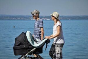 Couple protecting baby from coronavirus with a pram cover